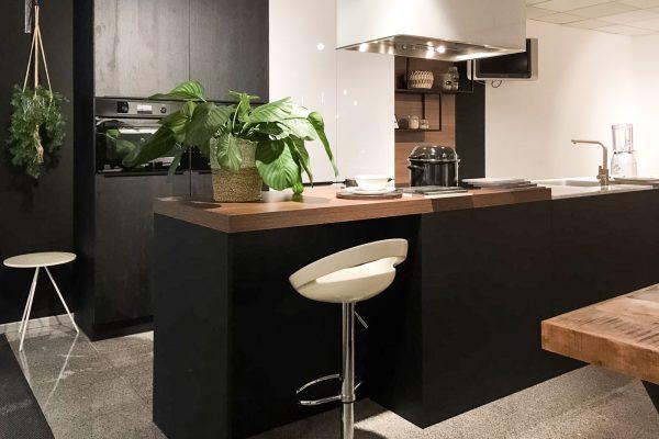 Zwarte keuken met kookeilend en houten werkblad